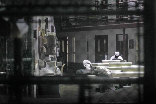 An unidentified prisoner reads a newspaper in a communal cellblock at Camp VI, a prison used to house detainees at Guantanamo Bay U.S. Naval Base