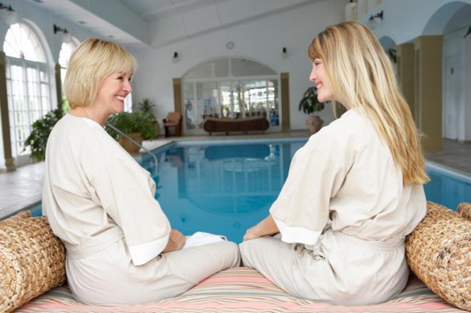 Two Women Relaxing By Swimming Pool