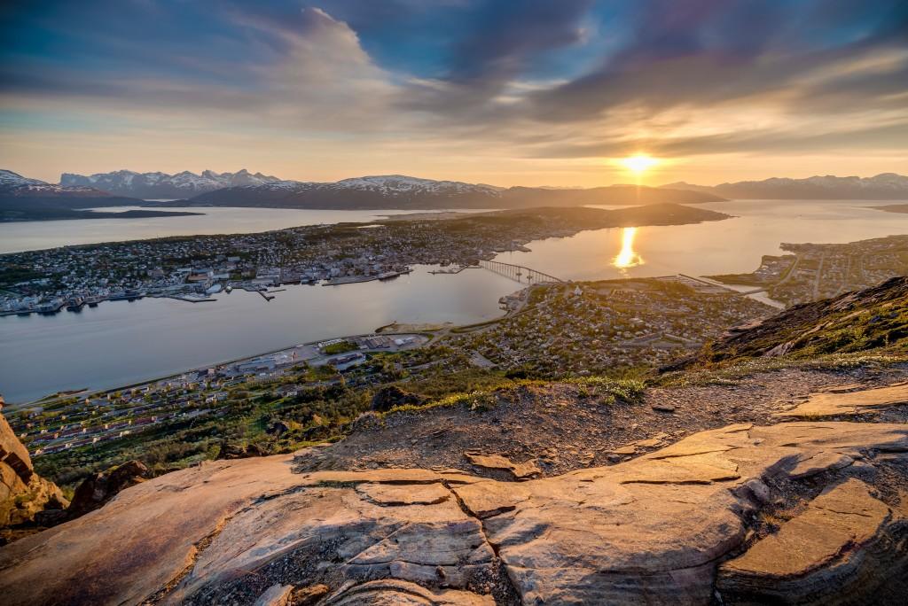 Tromso city in Tromsoya Island as seen from Mount Storsteinen under the Midnight Sun in Norway.