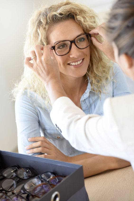 67015556 - blond woman at the optical shop, trying eyeglasses on