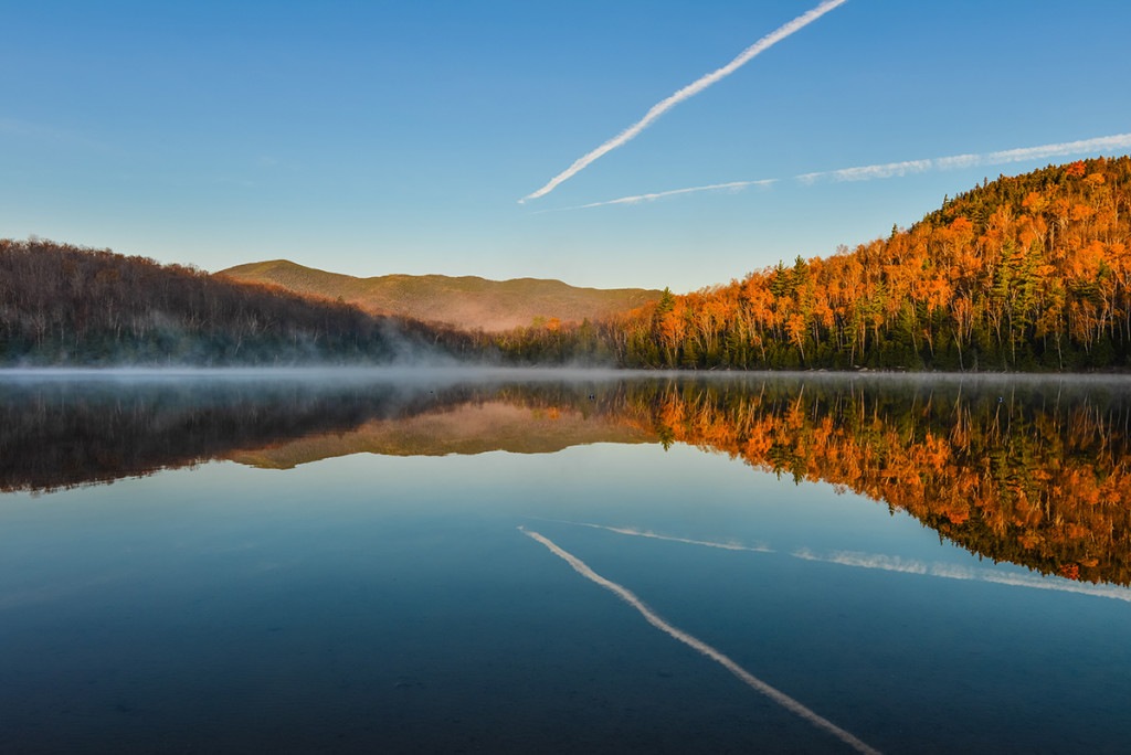Lake Reflections of fall foliage. Colorful autumn leaves shed reflected on the calm waters of Heart Lake in Lake Placid